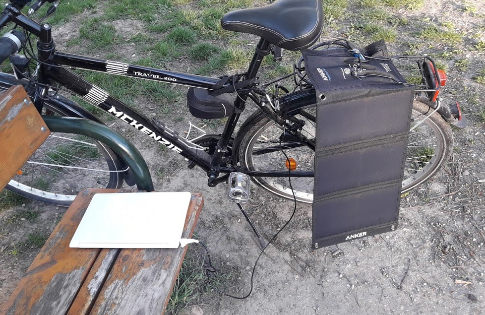 Solar panel dangling off a bike, Laptop connected to solar panel